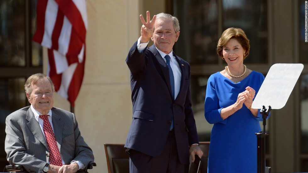 "George W. Bush gestures a ""W"" to the crowd after speaking."