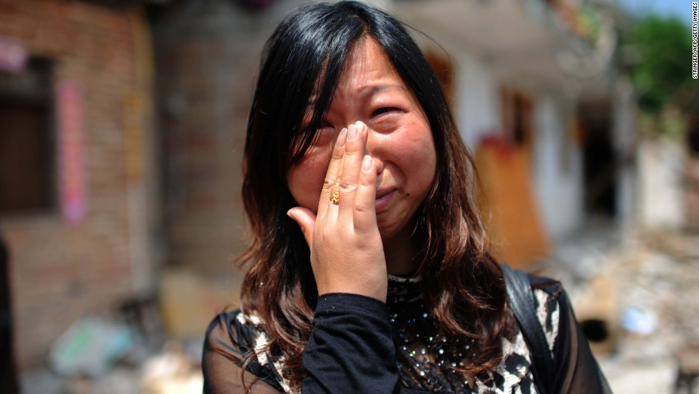 A woman who lost her son in the earthquake cries in front of her damaged home in Ya'an on April 24.