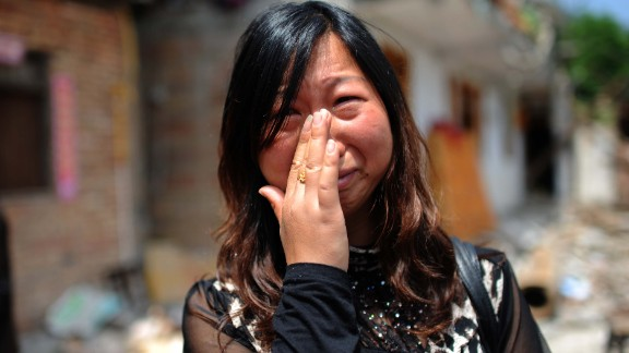 A woman who lost her son in the earthquake cries in front of her damaged home in Ya