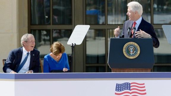 Former President George W. Bush and former first lady Laura Bush laugh during former President Bill Clinton's speech.