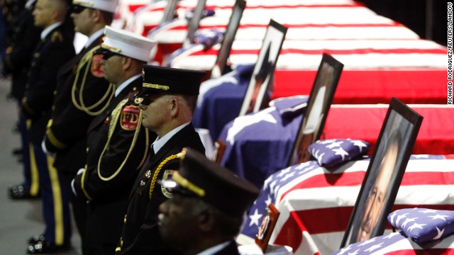 An honor guard of firefighters stand before the coffins of fallen firefighters on April 25.