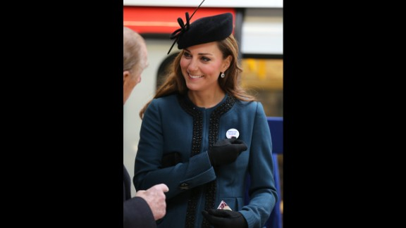 """To mark the 150th anniversary of the London Underground on March 20, the Duchess of Cambridge visits the Baker Street Underground Station, wearing a pin that reads, """"Baby on Board!"""""""
