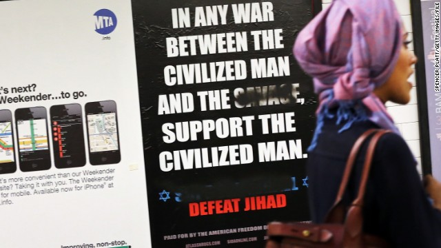 "A woman walks by a controversial ad in a New York subway station last fall. The word ""savage"" had been defaced."