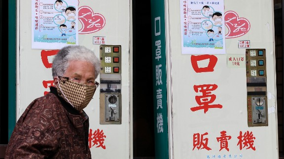 A woman wearing a medical mask walks past vending machines that sell masks outside National Taiwan University Hospital in Taipei on April 26. A 53-year-old Taiwanese businessman has contracted the H7N9 strain of bird flu while traveling in China, Taiwan