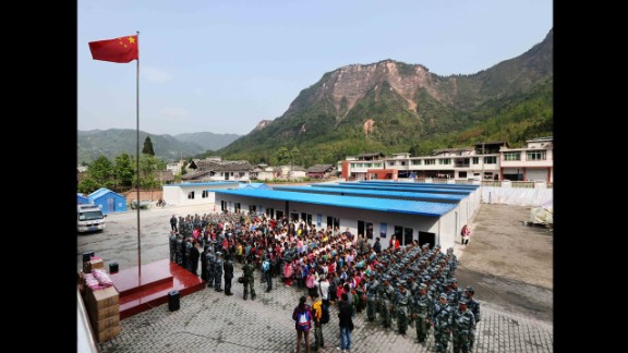 Students and soldiers from the air force attend a flag-raising ceremony in Baosheng Primary School in Lushan County, southwest China