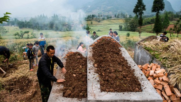 People pay their respects at a newly built grave in Ya
