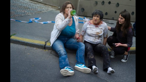 Two women injured in the explosion sit on the sidewalk.