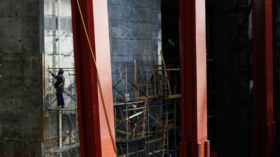 A worker stands on a scaffolding near the base of the construction on December 9, 2010.