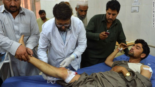 Pakistani paramedics treat an injured man following a bomb blast in Peshawar on April 29, 2013.