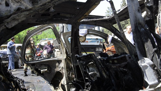 Caption:  A Syrian officer is seen through the wreckage of a vehicle following an explosion in the Mazzeh district of the Syrian capital Damascus on April 29, 2013, which is believed to have targeted the prime minister's convoy. Syrian Prime Minister Wael al-Halqi escaped an assassination bid, surviving a blast that targeted his convoy in Damascus, Syrian state television reported. AFP PHOTO/ LOUAI BESHARA (Photo credit should read LOUAI BESHARA/AFP/Getty Images)
