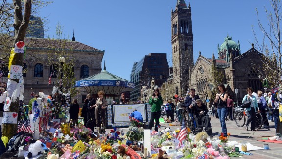People pause at the memorial site in Boston