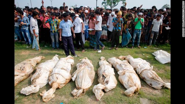 Unidentified bodies found in the rubble lie on the ground as people gather to watch a mass burial in Dhaka, on May 1.