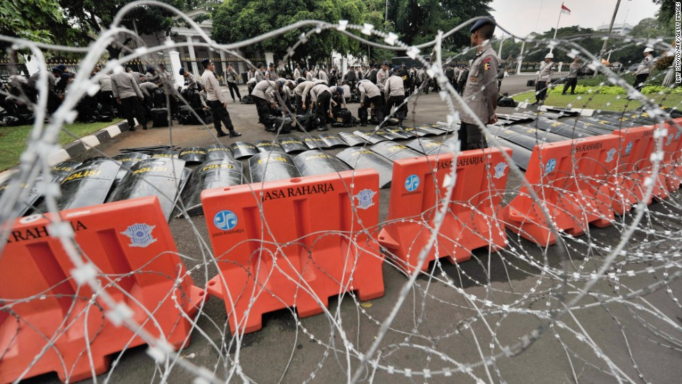 Police prepare behind a line of barbed wire before thousands of Indonesian workers arrive outside the presidential palace in Jakarta.