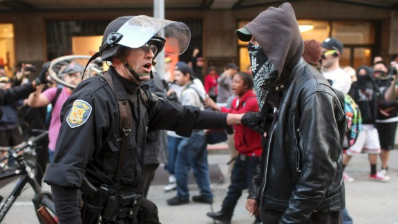 A police officer and demonstrator clash during May Day demonstrations in Seattle on Wednesday, May 1. A peaceful protest turned violent, and police say they sprayed demonstrators with pepper spray after they threw everything from metal pipes to fireworks at officers. Hundreds of thousands of people across the globe take to the streets on May 1 to demand better working conditions during what is known as International Workers