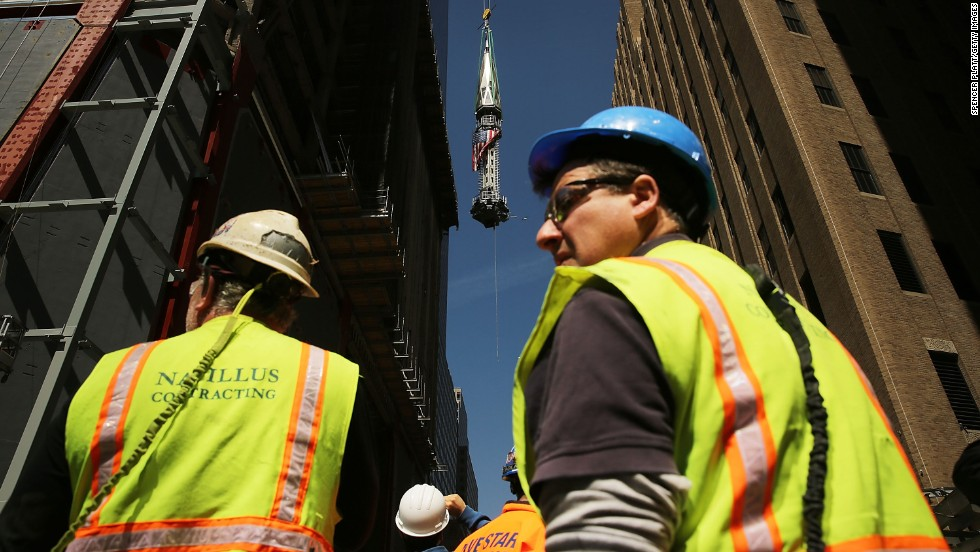 Construction workers watch as the 408-foot spire is hoisted onto a temporary platform on the top of One World Trade Center.