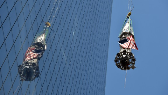 The final section of the spire is raised to the top of One World Trade Center.