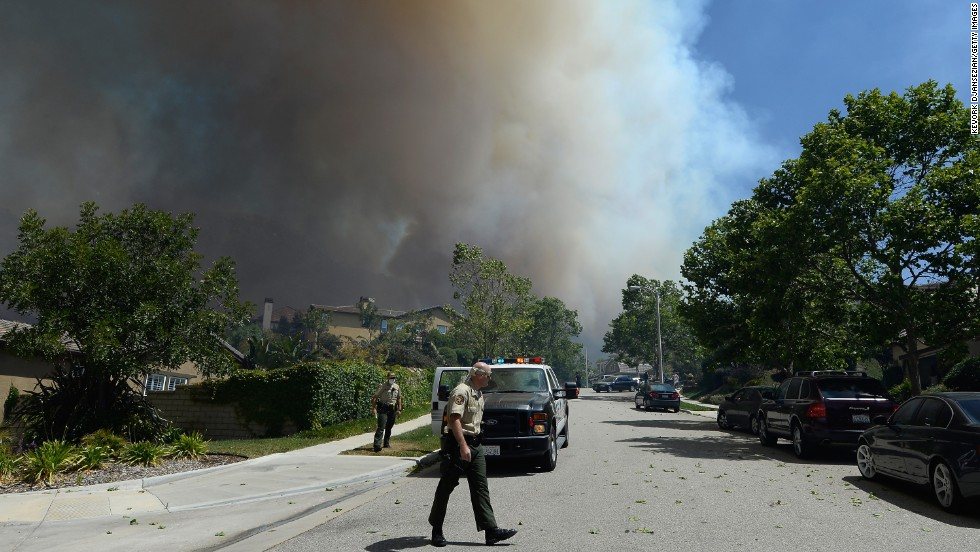 Ventura County fire officials go door-to-door asking residents if they need assistance as a wildfire approaches homes on Thursday. The wildfire has burned 6,500 acres.