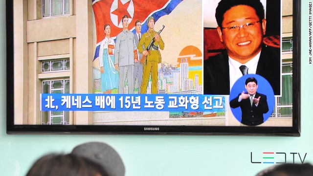 Passersby watch a report in Seoul on May 2 of Kenneth Bae, right, a Korean-American tour operator.