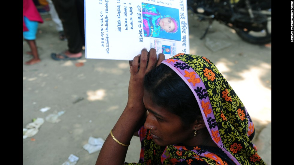 A woman holds up a picture of a missing person believed to be trapped in the rubble on May 3.