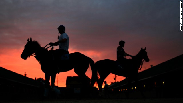 Horses walk around the stable as the sun rises over Churchill Downs in Louisville, Kentucky, on Friday, May 3 during morning workouts for the 2013 Kentucky Derby.
