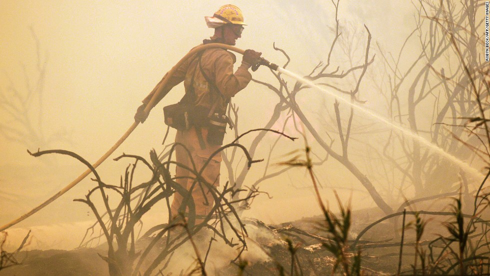 A firefighter sprays water on a flareup along the Pacific Coast Highway in Point Mugu, California, on May 3.