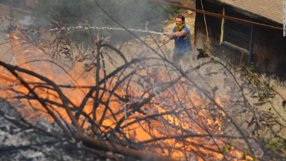 Homeowner Brian Bonsant uses a hose as flames get close to his barn during the second day of the Springs Fire in the mountain areas of Ventura County, California, on May 3. Hundreds of firefighters continue to battle wind and dry conditions as the fires continue to burn.