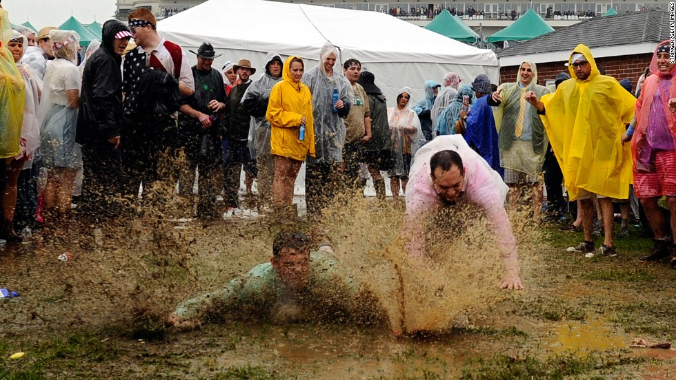 Fans decide that the muddy infield is the perfect place to practice thier sliding skills.