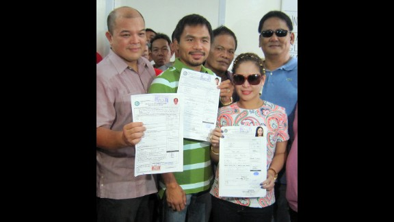 Pacquiao, center, and his wife Jinkee, right, display their certificates of candidacy at the election office in Alabel, Sarangani province, in the southern island of Mindanao, on October 2, 2012. Pacquiao registered to run for reelection as a congressman for the southern province of Sarangani, with Jinkee filing to stand for vice-governor.