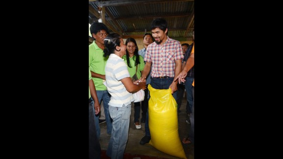 Pacquiao gives a sack of rice and relief goods to a woman after floods struck in Glan, Sarangani province, southern Philippines, June 17, 2012.