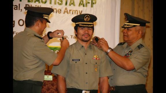 Pacquiao is conferred the rank of lieutenant colonel by Maj. Gen. Emmanuel Bautista, left, and Brig. Gen. Alex Albano, right, in Manila, on December 5, 2011.