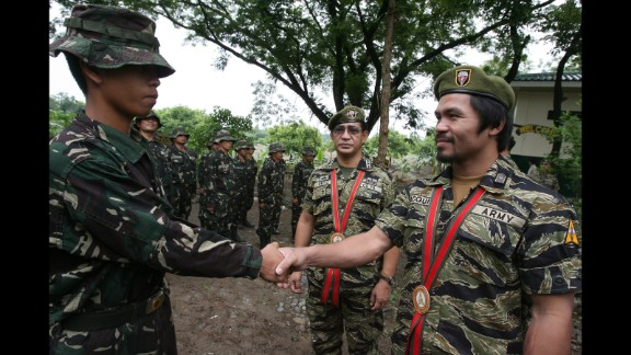"""Pacquiao shakes hands with a Special Forces Operation Course student during the 49th Special Forces Regiment anniversary at Fort Magsaysay in Nueva Ecija, north of Manila, on June 27, 2011. During the event, Pacquiao received the Honorary Special Forces Warrior Badge, and wore the exclusive Special Forces uniform popularly known as the """"Tiger suit."""""""