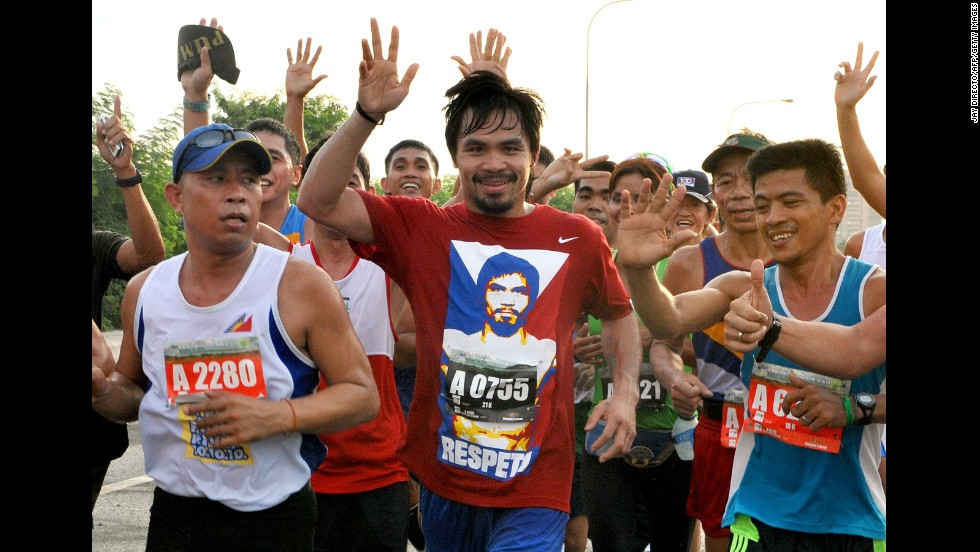 Pacquiao waves as he joins hundreds of other runners in Manila on October 10, 2010, to raise funds and environmental awareness to help revive the Pasig River, a heavily polluted major waterway that cuts through the city of 12 million.