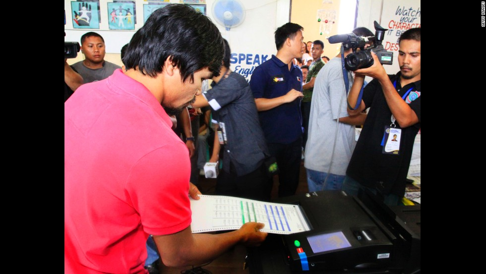 Pacquiao places his ballot into a vote-counting machine in Kiamba, Sarangani province, on May 10, 2010.
