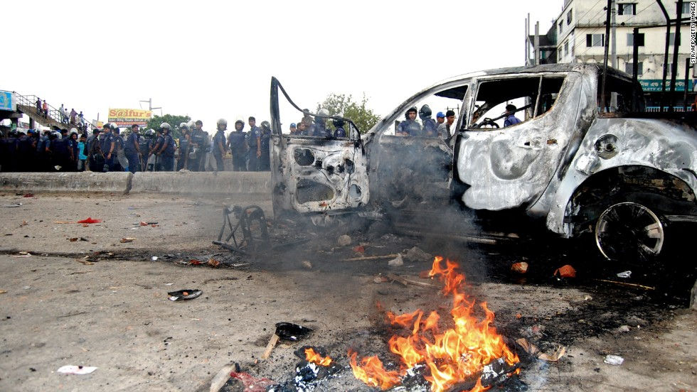 "Bangladeshi police gather near a car set ablaze by Islamist protesters during clashes on Monday, May 6. Police broke up a protest of tens of thousands of religious hardliners and shut down an Islamist television station Monday after battles in the streets of Dhaka. <a href=""http://www.cnn.com/2013/05/05/world/asia/bangladesh-clashes/index.html"">Demonstrations calling for religious laws</a>, led by the ultraconservative group Hefazat-e-Islam (Protectors of Islam), have been building since February."