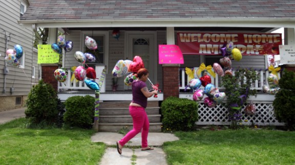 A relative of DeJesus brings balloons to the home of Amanda Berry