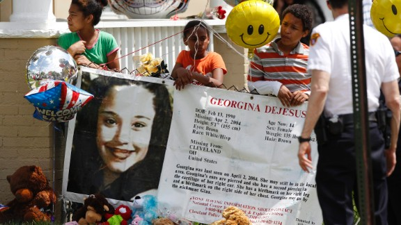 Children hold a sign and balloons in the yard of Gina DeJesus