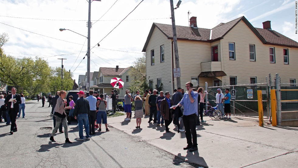 Bystanders and media gather on May 7 along Seymour Avenue in Cleveland near the house where the three women were held captive.