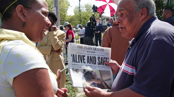 A bystander shows the front page of The Plain Dealer newspaper to a friend outside of the house on Seymour Avenue on May 7.
