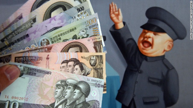 North Korean currency purchased at a Chinese border town is displayed in front of a painting in Beijing.