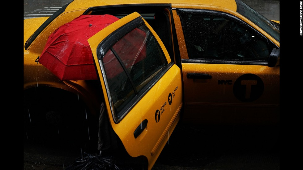 A woman exits a cab during a rainstorm on Wednesday, May 8, in New York.