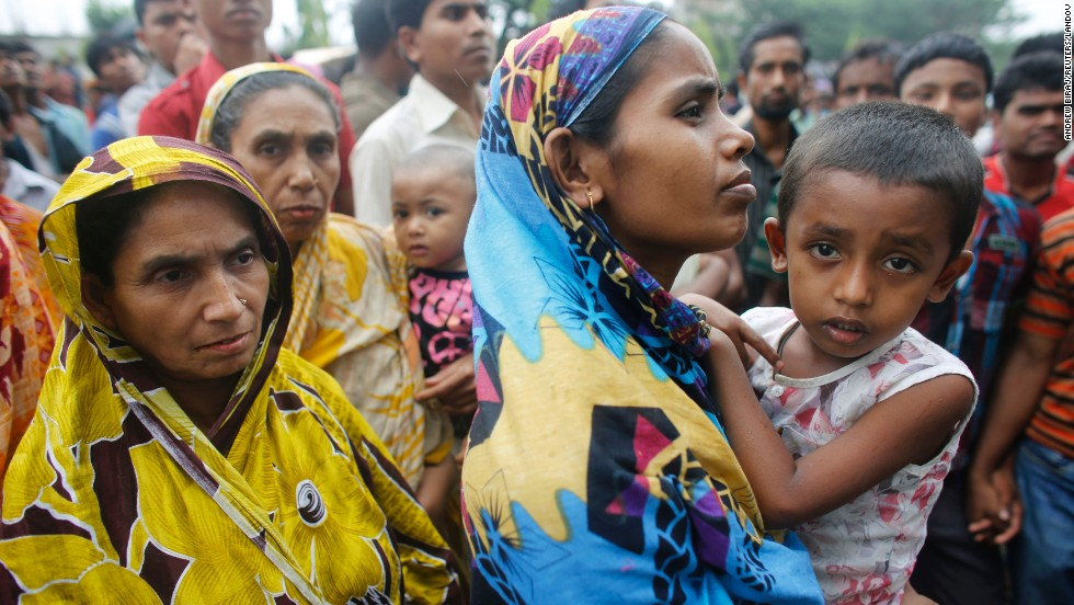 Relatives of garment workers gather in front of the factory.