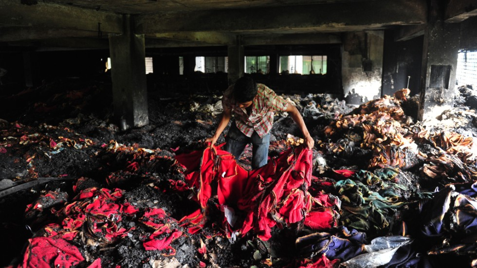 A Bangladeshi garment worker holds up burnt cloth inside the gutted factory in Dhaka.