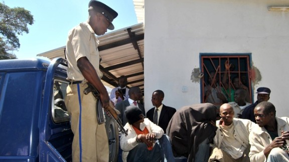 Philip Mubiana (covering his face) and James Mwape (left) arrive at the Kapiri magistrate court on May 8, 2013 in Lusaka.