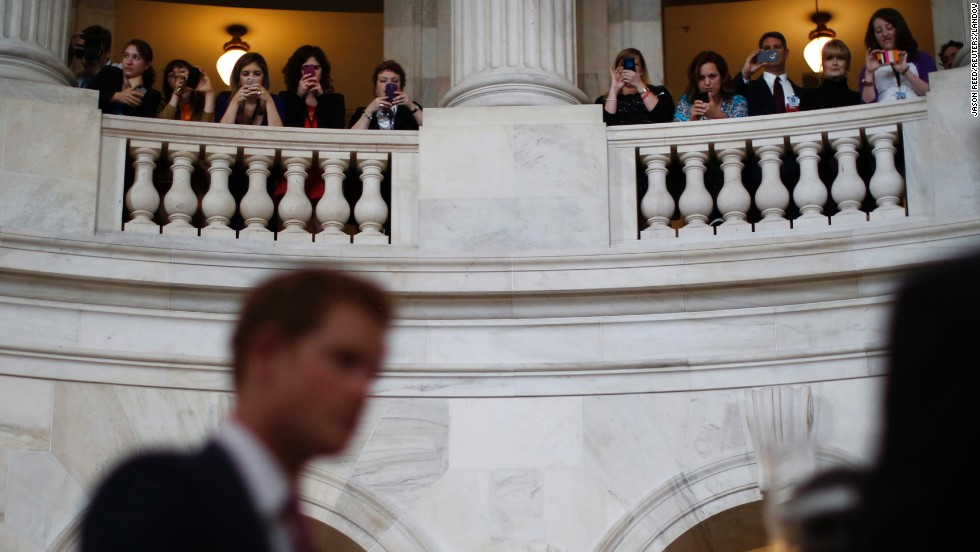 Capitol Hill staffers take pictures of Prince Harry from the balcony of the Russell Senate Office Building on May 9.