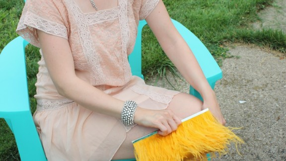 J.Crew personal stylist Caitlin Riley put together a 1920s look with a faux bob hairstyle, deep red lipstick, art deco accessories and a yellow feather clutch. Riley blogs about fashion with her twin sister, Valerie Efta.