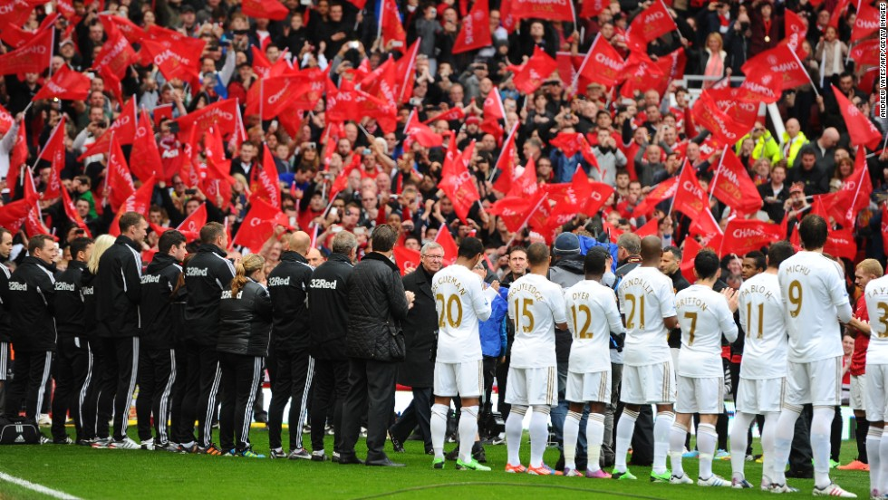 Ferguson walked onto the pitch at Old Trafford through a guard of honor formed by the United and Swansea City players.