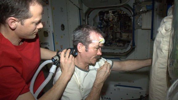 """Hadley got a space haircut as depicted in this April 7 photo. """"Dr. Tom doing a nice, surgical job of trimming, working around the science experiment (temperature) sensor,"""" Hadfield tweeted."""