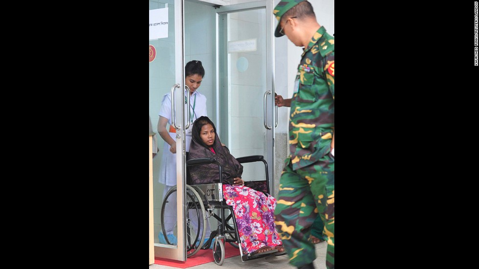 A nurse helps Begum through a door as she attends a media conference at the Savar Combined Military Hospital in Dhaka on May 13.