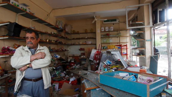 A shop owner stands in his damaged shop on Monday, May 13, at the site of a deadly twin bomb blast in the town of Reyhanli in Hatay province, near the Turkish-Syrian border. Turkey has blamed Marxists with Syrian connections for the May 11 attacks.