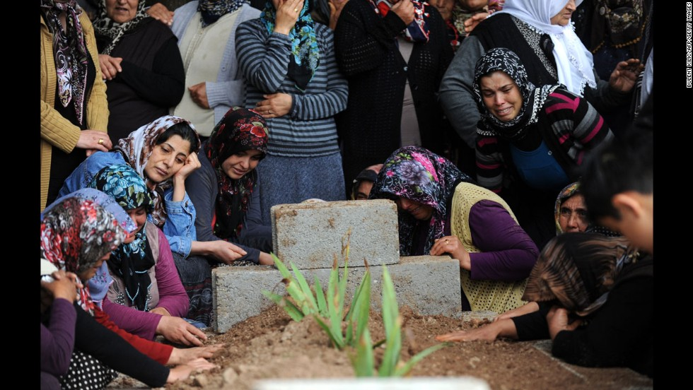 Relatives mourn at the grave of a bombing victim on May 12.  Residents of Reyhanli called on Turkey's government to step down, alleging that it has gotten their country too involved Syria's troubles.
